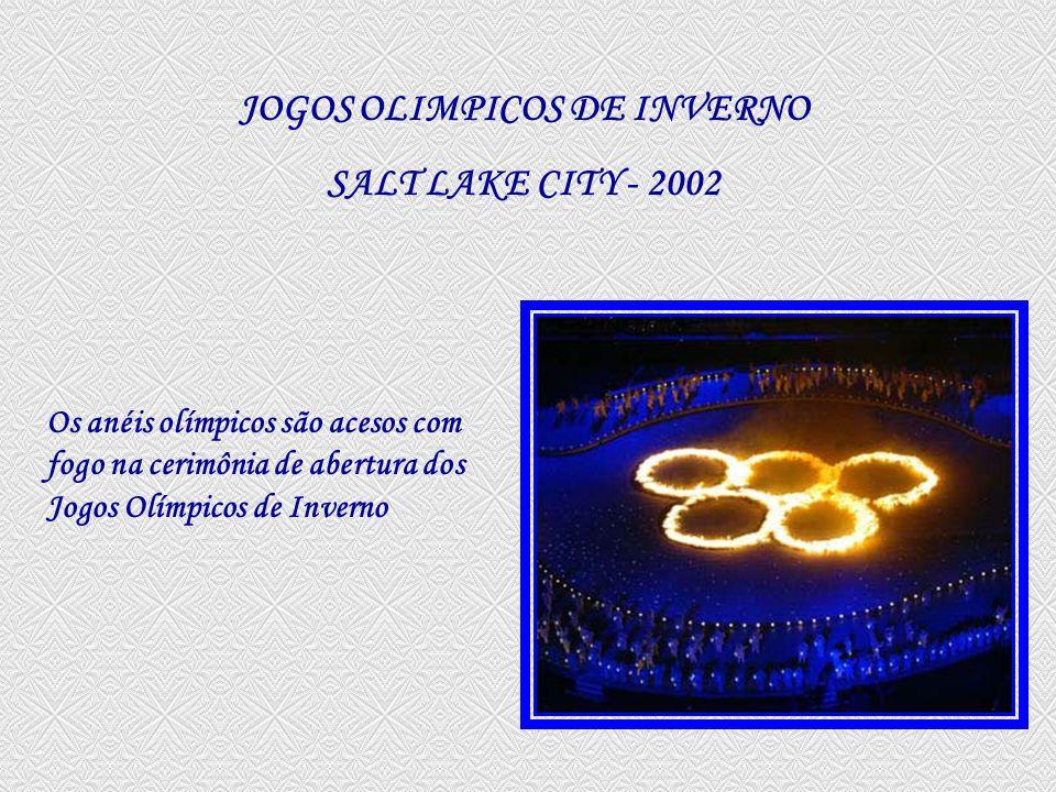 A tocha olímpica no Estádio Olímpico de Salt Lake City; embaixo está a equipe dos EUA campeã em 1980 Fogos de artifício iluminam o Estádio Olímpico Rice-Eccles em Salt Lake City