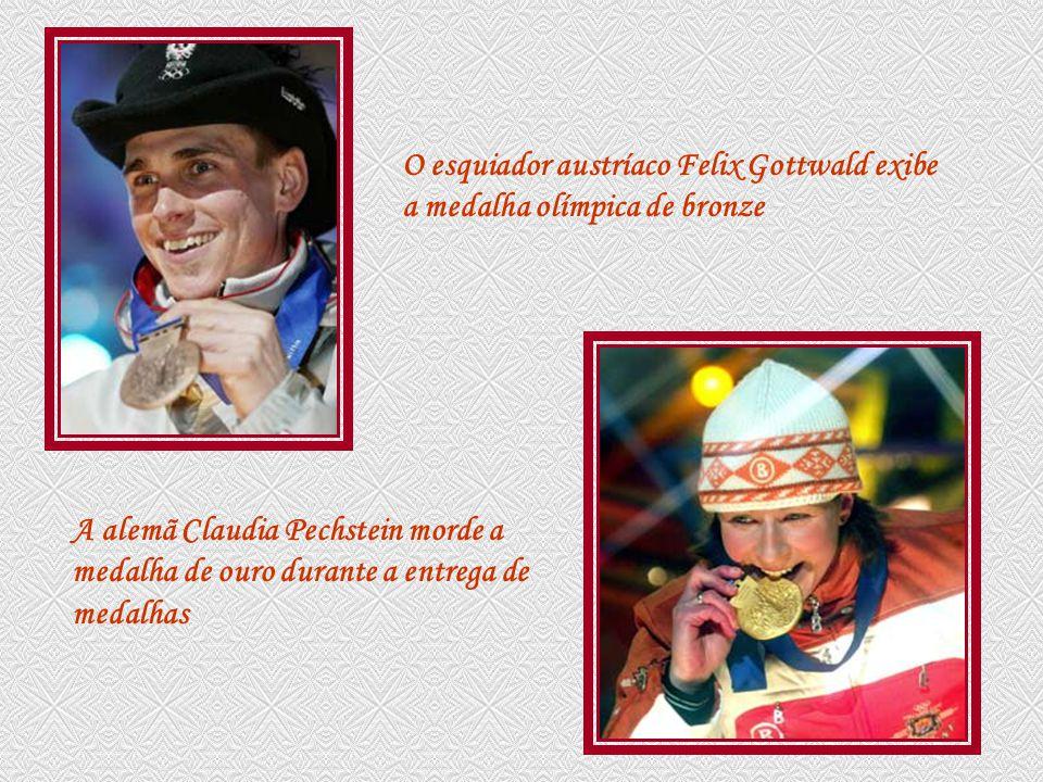 O esquiador austríaco Felix Gottwald exibe a medalha olímpica de bronze A alemã Claudia Pechstein morde a medalha de ouro durante a entrega de medalhas