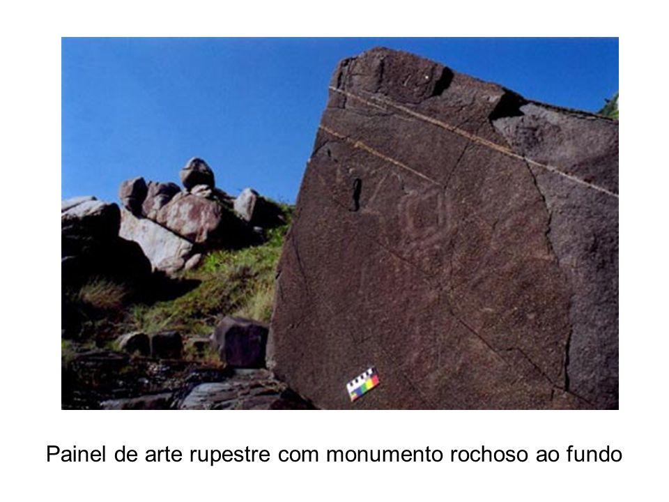 Painel de arte rupestre com monumento rochoso ao fundo