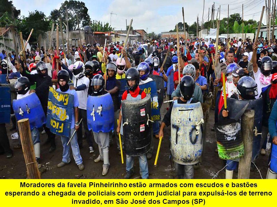 Moradores da favela Pinheirinho estão armados com escudos e bastões esperando a chegada de policiais com ordem judicial para expulsá-los de terreno in