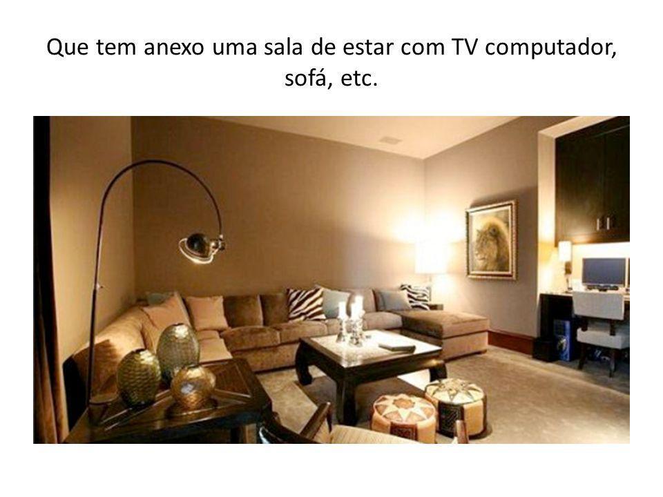 Que tem anexo uma sala de estar com TV computador, sofá, etc.