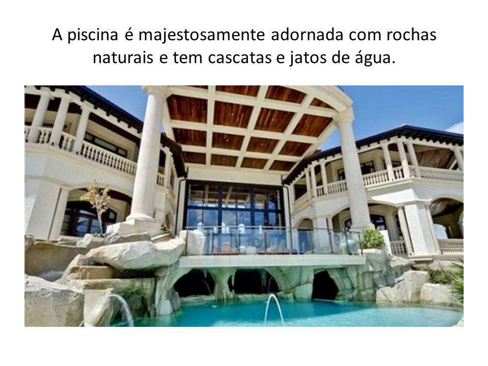 A piscina é majestosamente adornada com rochas naturais e tem cascatas e jatos de água.