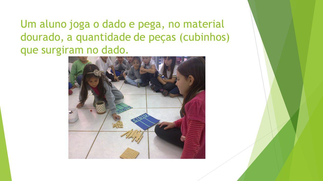 Um aluno joga o dado e pega, no material dourado, a quantidade de peças (cubinhos) que surgiram no dado.
