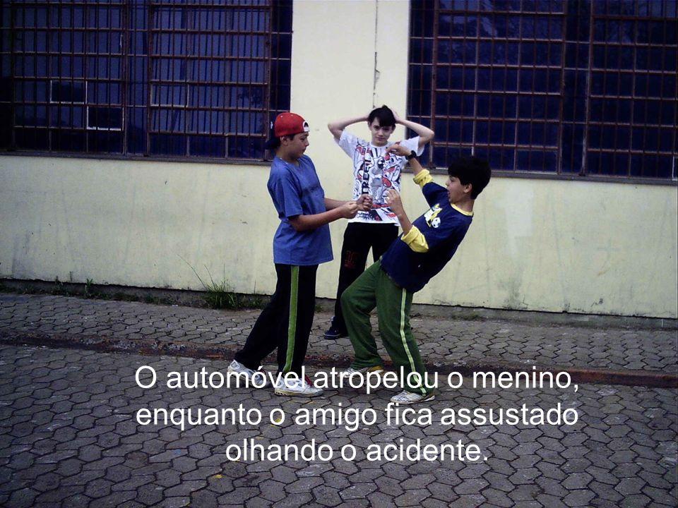 O automóvel atropelou o menino, enquanto o amigo fica assustado olhando o acidente.