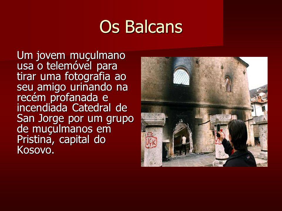 Os Balcans Um jovem muçulmano usa o telemóvel para tirar uma fotografia ao seu amigo urinando na recém profanada e incendiada Catedral de San Jorge por um grupo de muçulmanos em Pristina, capital do Kosovo.
